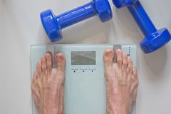 Man standing on scale. View of feet, lifting weights and blank scale royalty free stock image