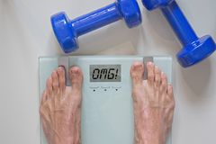 Man standing on scale. View of feet, lifting weights and text omg written on scale stock photography