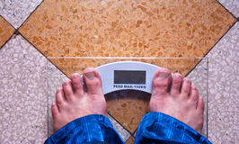 A man is standing on a scale Royalty Free Stock Photography