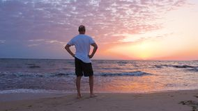 Man standing on sea beach and watching morning sunrise in multicolored sky stock footage