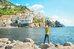 Man standing by sea looking at city view. Young caucasian man standing on rocks by sea with his back to camera enjoying view of small european coastal town Royalty Free Stock Photos