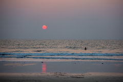 A man is standing in the sea at sunset. Landscape of the sunset. Landscape of a deserted beach, a man stands in the sea waist-deep in the water. Red sun and red Stock Images