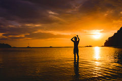 Man standing in sea and sunset Stock Image