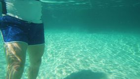 A man standing on the seabed. A pan to left shot of a man standing on the seabed. The man is wearing a blue swimming trunks stock video footage