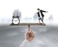 Man standing on seesaw vs clock Royalty Free Stock Image