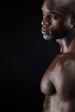 Man standing shirtless in the studio. Cropped shot of a man standing shirtless in the studio. African male model with muscular build on black background Stock Photo