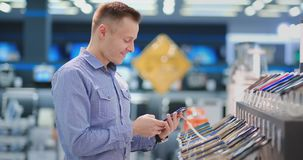 A man standing at a shop window with smartphones chooses a new phone model to buy a portable electronics store. Purchase. The latest version of the gadget stock footage