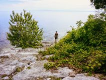 A man standing by the shore of Lake Ontario in Oakville, Ontari, Canada, staring out at the vast waters of the great lake. Deep in thought stock photos