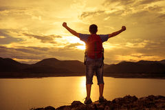 Man standing on the shore of a mountain lake and raises his arms Stock Image