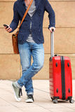 Man standing on sidewalk with mobile phone and suitcase. Cropped portrait of man standing on sidewalk with mobile phone and suitcase Royalty Free Stock Photography