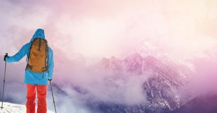 Man standing with skies on slope stock photography