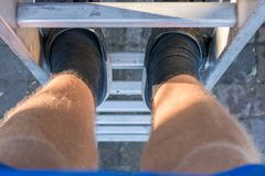 Wrong shoes on a ladder royalty free stock photos