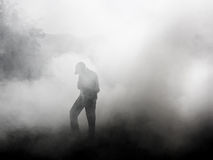 Man standing in smoke.