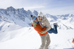 Man standing in snow lifting girlfriend with mountain in background Stock Images