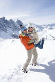Man standing in snow lifting girlfriend with mountain in background Stock Image