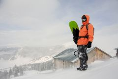 Man standing with the snowboard in hands on the hill near the ho. Man standing with the snowboard in hands onthe hill in the mountain in the popular tourist stock photos