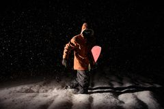 Man standing with the snowboard in the mountain resort in the ni stock photo