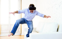 Man standing on sofa couch excited using 3d goggles watching 360 Royalty Free Stock Photography