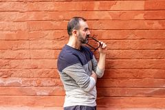 Man standing with some glasses in his mouth. In front of a red wall royalty free stock photos
