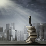 Man standing on a stack of books Royalty Free Stock Images