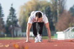 Man Standing in Starting Position for Running. Attractive Man Getting Ready for the Race in City Park Area - Training and Exercising for Endurance - Fitness Stock Photography