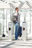 Man standing at station entrance with phone and luggage. Portrait of man standing at ticket turnstile with mobile phone and luggage Royalty Free Stock Image
