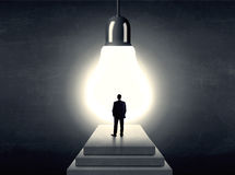 Man standing on a step in front of a huge light bulb Royalty Free Stock Image