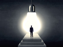 Man standing on a step in front of a huge light bulb Royalty Free Stock Images