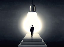 Man standing on a step in front of a huge light bulb Stock Photo
