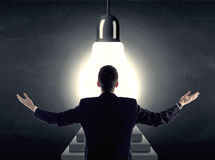 Man standing on a step in front of a huge light bulb Royalty Free Stock Photography