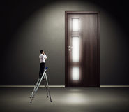 Man standing on stepladder and looking at the door Stock Photography