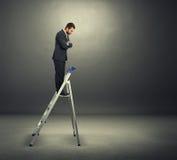 Man standing on the stepladder over dark Stock Photo