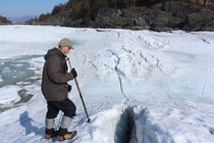 Man standing with sticks at a crack on a melting river. In the spring. Katun River, Altai, Russia Stock Photo