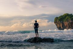 Man Standing on Stone Near Seashore during Sunrise Photography stock image