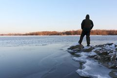 Man standing on stones at the freezing river at sunset. Ob River, Siberia, Russia Royalty Free Stock Photo