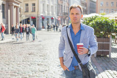 Man standing on the street with coffee in his hands Stock Photography