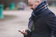 A man is standing in the street and waiting for someone. He looks at his phone and dials a number stock image