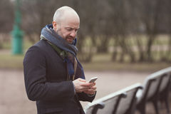A man is standing in the street and waiting for someone. He looks at his phone and dials a number royalty free stock image