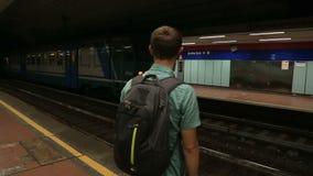 Man standing on subway platform, train passing station, public transportation. Stock footage stock footage