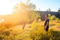 Man standing on summer green hill with trees at sunny day royalty free stock photos