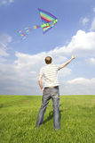 Man standing on summer lawn and playing with kite Stock Photos