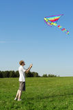 Man standing on summer meadow and flying kite Royalty Free Stock Image