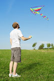 Man standing on summer meadow and flying kite Royalty Free Stock Photos