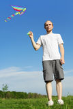 Man standing on summer meadow and flying kite Royalty Free Stock Images