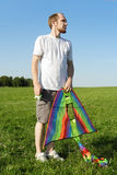Man standing on summer meadow and holding kite Stock Photography