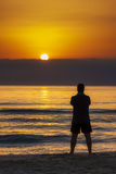 Man Standing Sunrise Sunset Beach Contemplation. Young man standing on the beach contemplating sunrise sunset behind wall of clouds stock photo