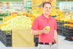 Man standing in a supermarket and holding an apple Royalty Free Stock Photo