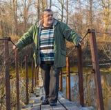 Man standing on a suspension bridge over Vorskla river in Ukraine Stock Photo