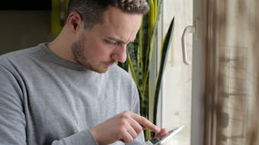 Man standing with tablet by the window at home stock footage