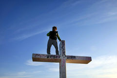 Man Standing on Tall Cross Stock Image